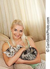 feliz, mujer joven, con, gato, stitting, en, sofá