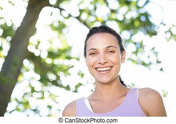 feliz, mujer joven, en el parque