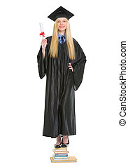 feliz, mujer joven, en, traje de ceremonia de entrega de diplomas, con, diploma, posición, en, montón libros
