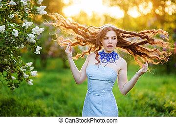 feliz, mujer joven, en, un, parque, en, primavera, lila, con, loosened, pelo