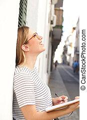feliz, mujer joven, escritura libro, exterior