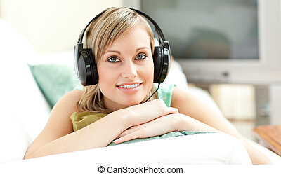 feliz, mujer joven, escuchar, música, acostado, en, un, sofá