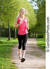 feliz, mujer joven, jogging, en el estacionamiento