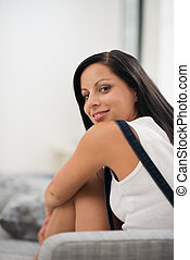 feliz, mujer joven, sentar sofá