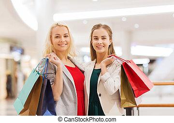 feliz, mujeres jóvenes, con, bolsas de compras, en, alameda