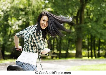 feliz, mulher jovem, com, bicicleta, parque