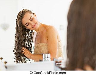 feliz, mulher jovem, com, cabelo molhado, em, banheiro