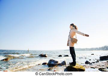 feliz, mulher jovem, com, mãos cima, dia ensolarado, ligado, a, praia.