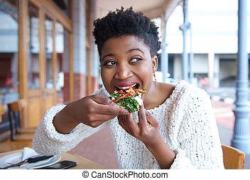 feliz, mulher jovem, comendo pizza, em, restaurante