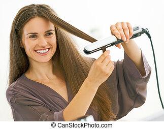 feliz, mulher jovem, endireitar, cabelo, com, straightener