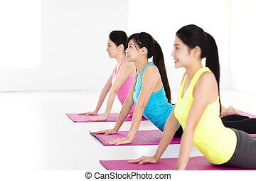feliz, mulher jovem, grupo, fazendo, ioga, exercícios