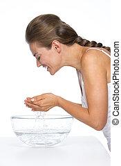 feliz, mulher jovem, lavando rosto, em, bacia vidro, com, água