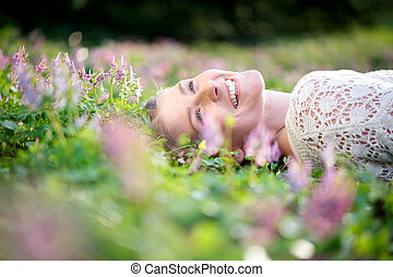 feliz, mulher jovem, mentindo, em, prado, de, flores