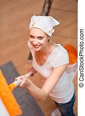 feliz, mulher jovem, quadro, um, parede, em, cor alaranjada