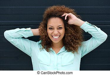 feliz, mulher jovem, sorrindo, ao ar livre, contra, experiência preta