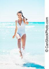 feliz, mulher jovem, tocando, com, água, em, litoral