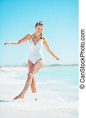 feliz, mulher jovem, tocando, com, água, ligado, praia
