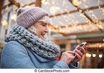 feliz, mulher sênior, usando, telefone móvel, ligado, rua