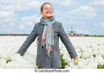 feliz, niña, en, tulipanes