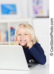 feliz, niña joven que sonríe, mientras, utilizar, un, computador portatil