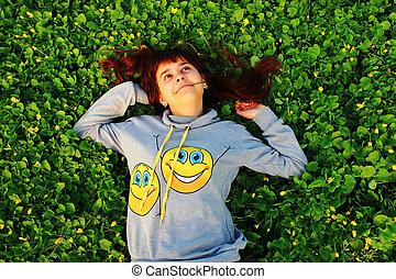 feliz, niña, mentira en la hierba