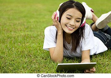 feliz, niña, utilizar, computadora personal tableta, en la hierba