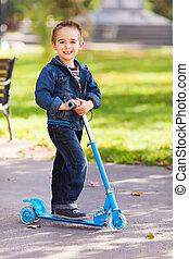 feliz, niño, con, patineta, en, patio de recreo