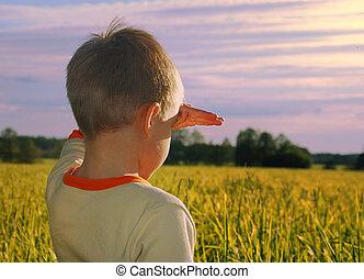 feliz, niño joven, mirar, horizonte, en, puesta de sol