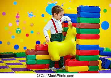feliz, niño, jugar juguetes, en, jardín de la infancia