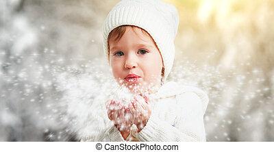 feliz, niño, niña, soplar, copos de nieve, en, invierno, aire libre