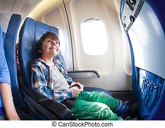 feliz, niño pequeño, en, asiento del aeroplano, sentarse, por, ventana