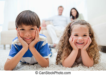 feliz, niños, acostado, alfombra, con, padres, atrás, ellos