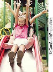 feliz, niños, diapositiva, en, patio de recreo