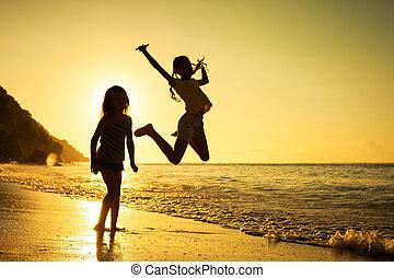 feliz, niños, juego, en, playa, en, el, salida del sol, tiempo