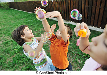 feliz, niños jugar, con, burbujas, al aire libre, foco selectivo, -, cabritos en el movimiento