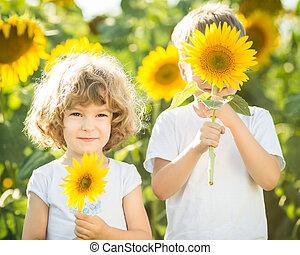feliz, niños jugar, con, girasoles