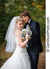 feliz, novia y novio, en, un, boda, en el parque