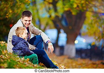feliz, pai filho, sentando, em, outono, parque