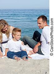 feliz, pais, com, seu, filho, sentando, areia