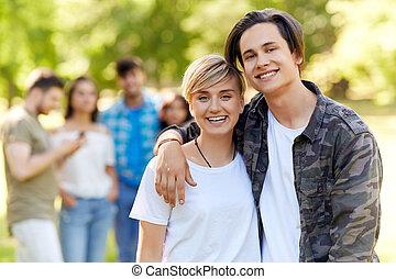 feliz, par adolescente, abraçando, em, verão, parque
