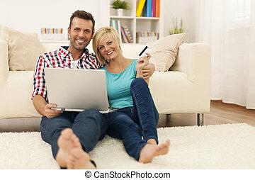 feliz, par amoroso, sentar chão, e, usando computador portátil, e, mostrando, cartão crédito
