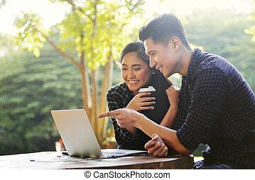 feliz, par asiático, olhar, algo, ligado, um, laptop