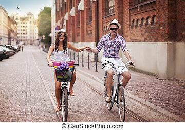 feliz, par jovem, segurar passa, e, montando, ligado, bicicleta