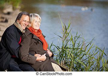 feliz, par velho, desfrutando, a, sol, perto, um, lago
