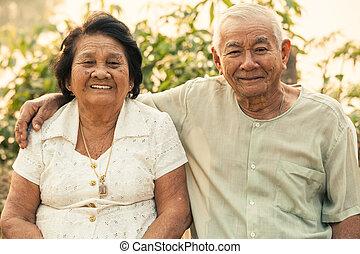 feliz, par velho, sentando, ao ar livre