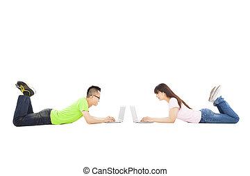 feliz, pareja joven, acostado, juntos, con, computador portatil