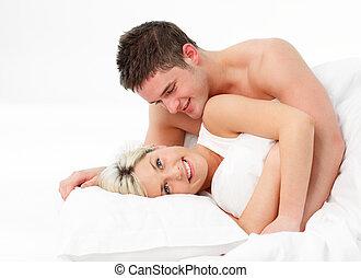 feliz, pareja joven, en cama