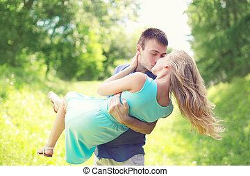 feliz, pareja joven, es, besar, hombre y mujer, enamorado, asideros, en, un, manos, en, pasto o césped, aire libre