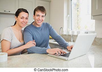 feliz, pareja joven, usar la computadora portátil