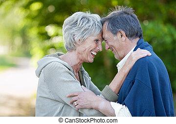 feliz, pareja mayor, con, cabeza dirigir, sonriente, en el estacionamiento